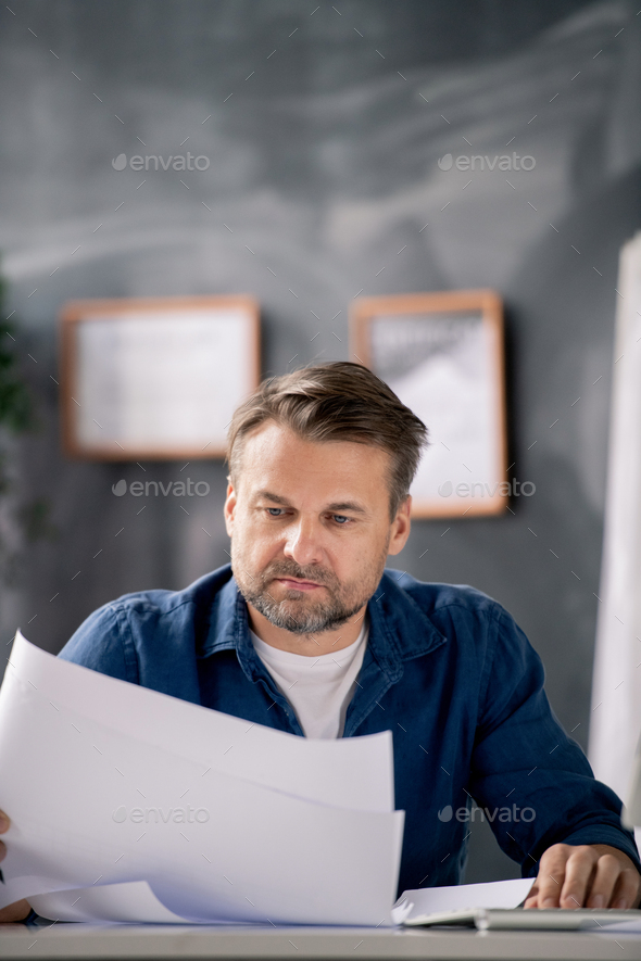 Bearded middle aged architect in casualwear looking at blueprint with sketch - Stock Photo - Images