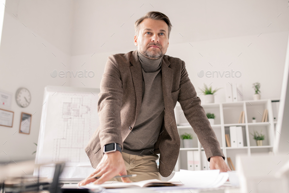 Pensive mature architect leaning against desk with papers while planning work - Stock Photo - Images
