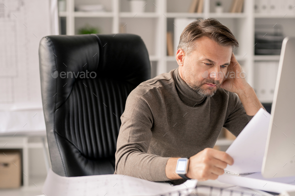 Mature engineer with papers looking at one of sketches while checking them - Stock Photo - Images