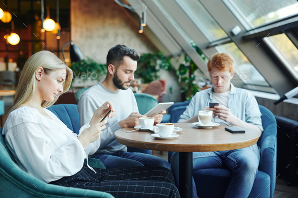 Pretty blonde girl and two guys using mobile gadgets while relaxing in cafe - Stock Photo - Images