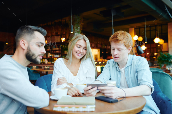 Young friends having coffee and watching curious video in smartphone in cafe - Stock Photo - Images