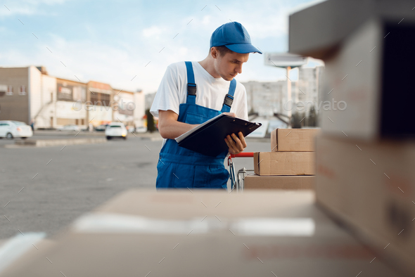 Deliveryman in uniform check parcels, delivery - Stock Photo - Images