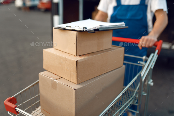 Deliveryman holds cart with stack of boxes - Stock Photo - Images