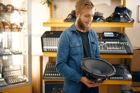 Musician buying subwoofer speaker in music store - Stock Photo - Images