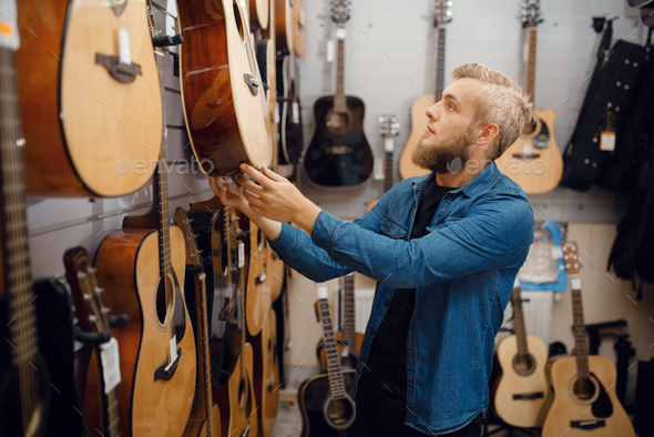 Bearded young man choosing a guitar in music store - Stock Photo - Images