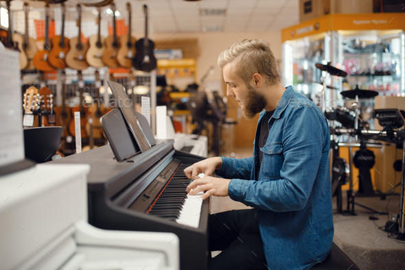 Musician trying to play on piano in music store - Stock Photo - Images