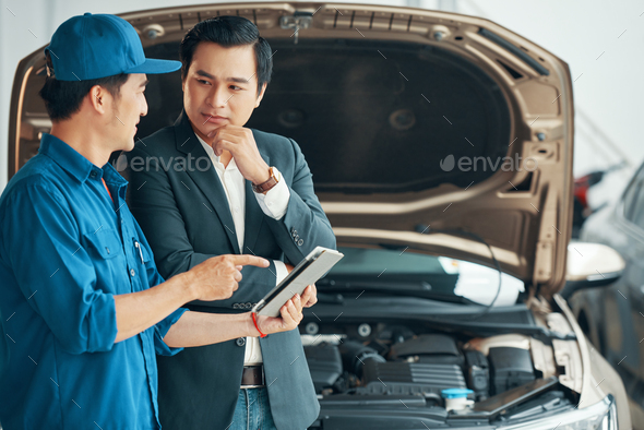 Men discussing the problem of car motor - Stock Photo - Images