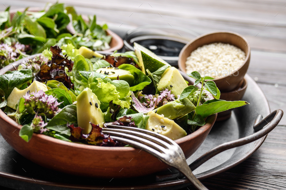 Clay dish with salad of avocado, green and violet lettuce, lamb' - Stock Photo - Images