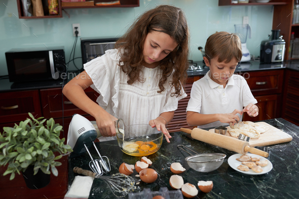 Brother and sister making cookies - Stock Photo - Images