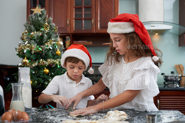 Siblings cutting cookie dough - Stock Photo - Images