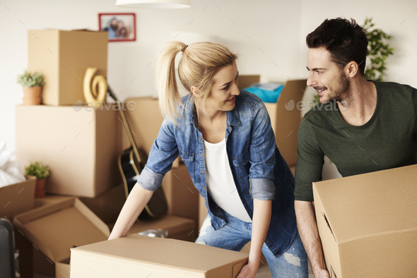 Loving couple unpacking stuff from cartons - Stock Photo - Images