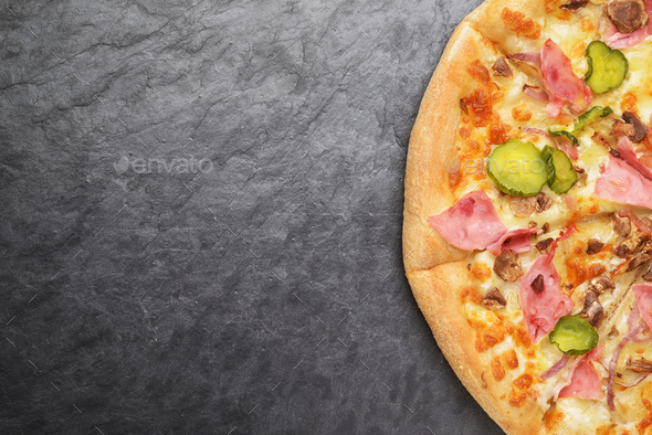 Pizza with ham, pickles, onion, mushrooms and cheese on the blac - Stock Photo - Images