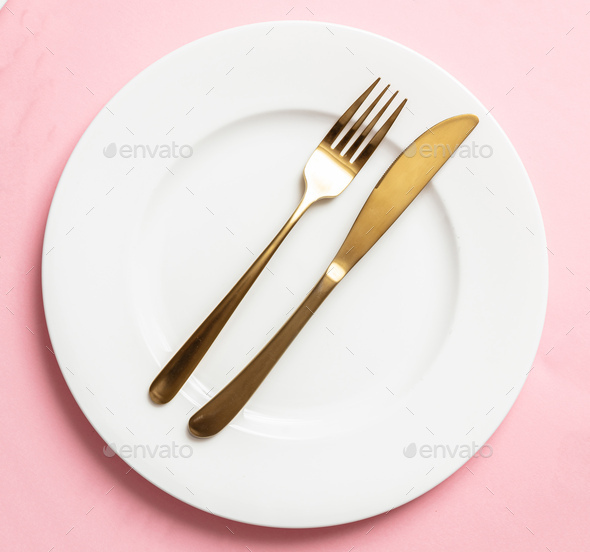 Gold cutlery and dishes set against pink background, formal place setting - Stock Photo - Images