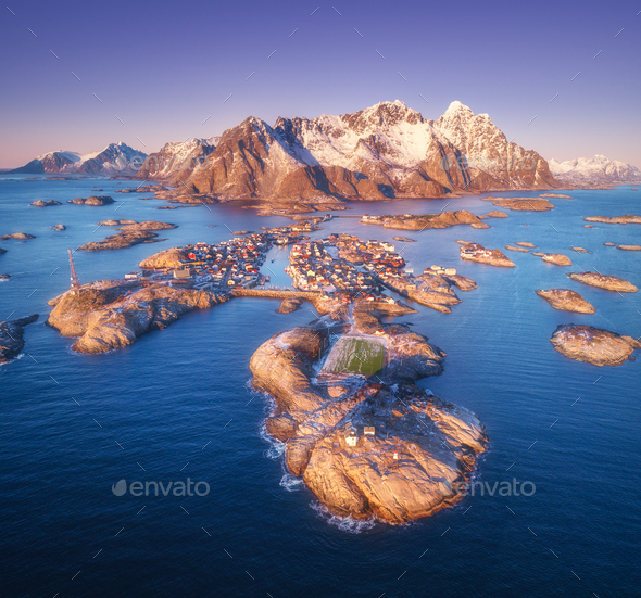 Aerial view of rocks in sea, snowy mountains, purple sky - Stock Photo - Images