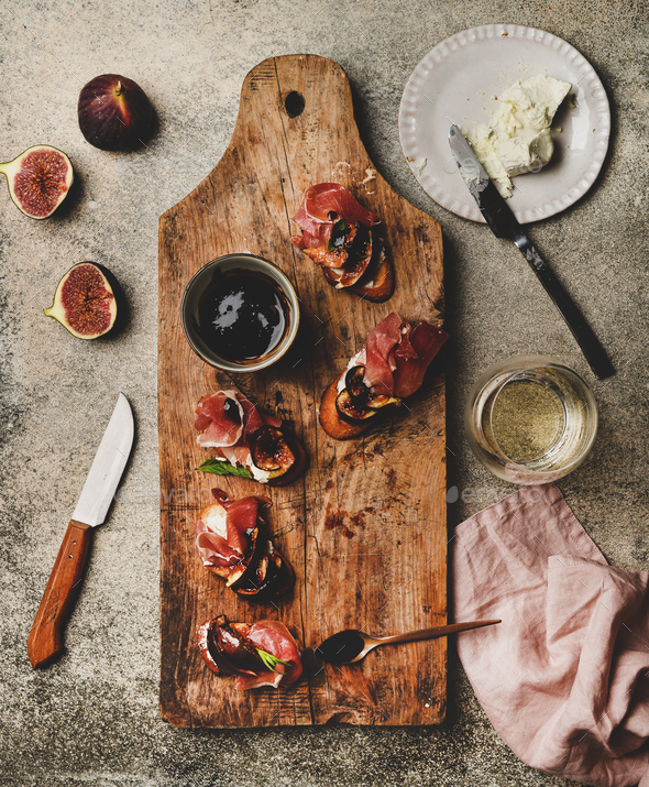 Crostini with prosciutto and glass of wineon wooden board - Stock Photo - Images
