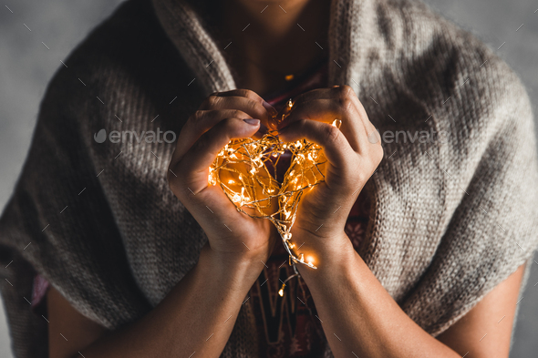lights in the palms. Women's hands holding a garland. Girl in a red dress with Christmas lights - Stock Photo - Images
