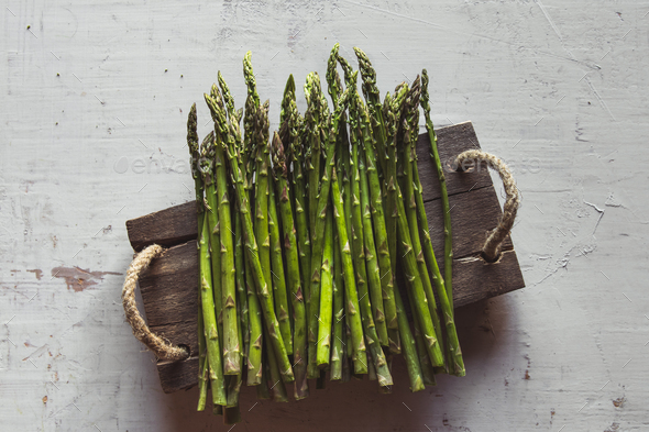 asparagus on a cut board on an old white background - Stock Photo - Images