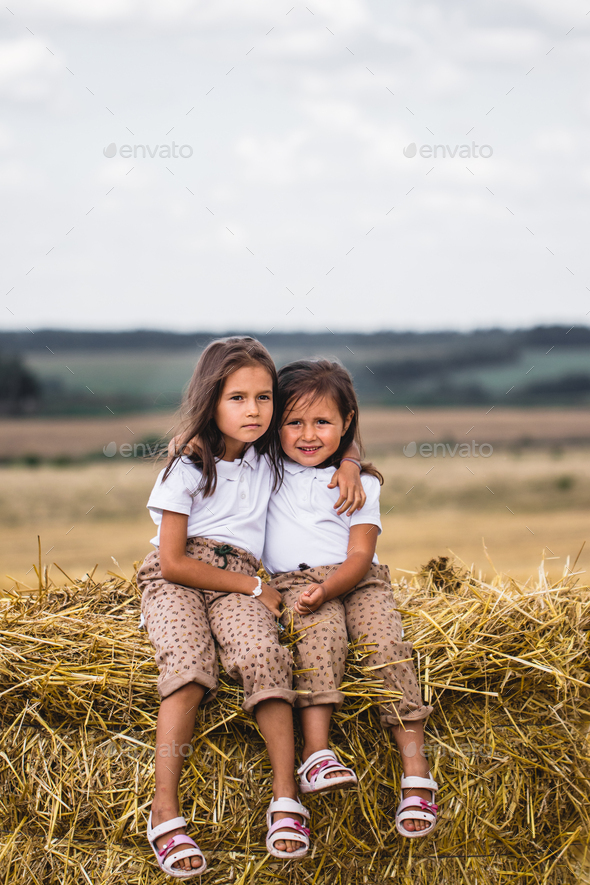 Two girls sitting on a bale of hay - Stock Photo - Images