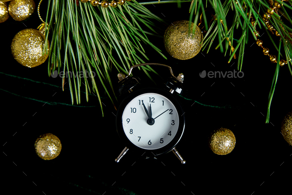 Black Alarm clock and fir tree branch, gold christmas decorations green velours - Stock Photo - Images