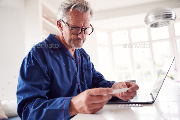 Mature Man At Home Looking Up Information About Medication Online Using Laptop - Stock Photo - Images