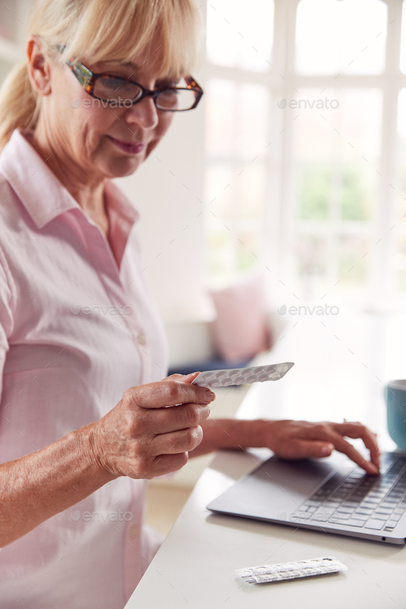 Mature Woman At Home Looking Up Information About Medication Online Using Laptop - Stock Photo - Images