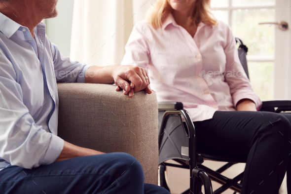 Close Up Of Mature Couple With Woman In Wheelchair Sitting In Lounge At Home Holding Hands Together - Stock Photo - Images