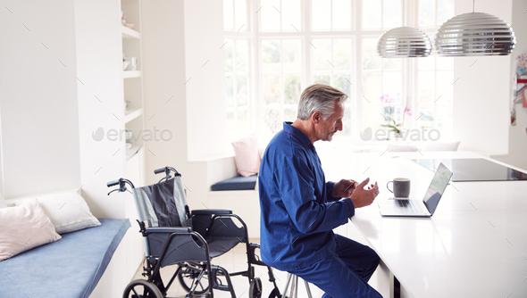 Mature Disabled Man In Wheelchair At Home Using Laptop On Kitchen Counter - Stock Photo - Images