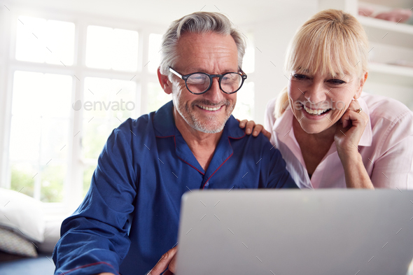 Mature Couple At Home Looking Up Information About Medication Online Using Laptop - Stock Photo - Images