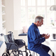 Mature Disabled Man In Wheelchair At Home Using Laptop On Kitchen Counter - PhotoDune Item for Sale