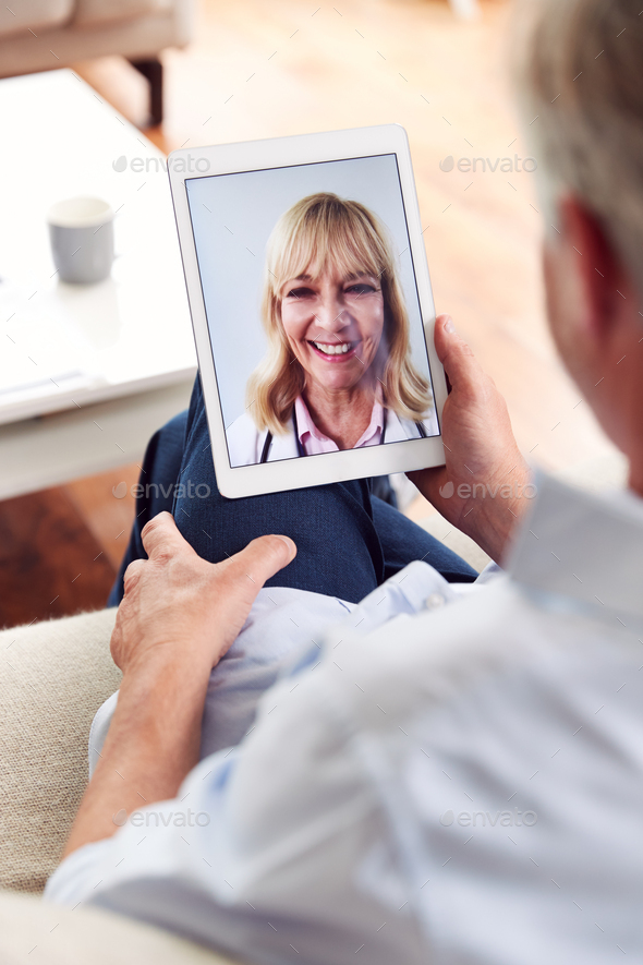 Mature Man Having Online Consultation With Female Doctor At Home On Digital Tablet - Stock Photo - Images