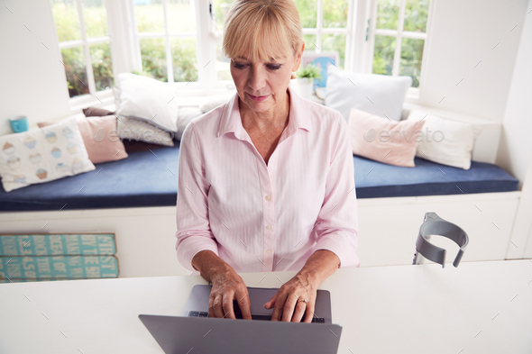 Mature Disabled Woman With Crutches At Home Working On Laptop On Kitchen Counter - Stock Photo - Images