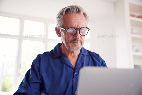 Serious Mature Man Looking Up Information Online Using Laptop - Stock Photo - Images