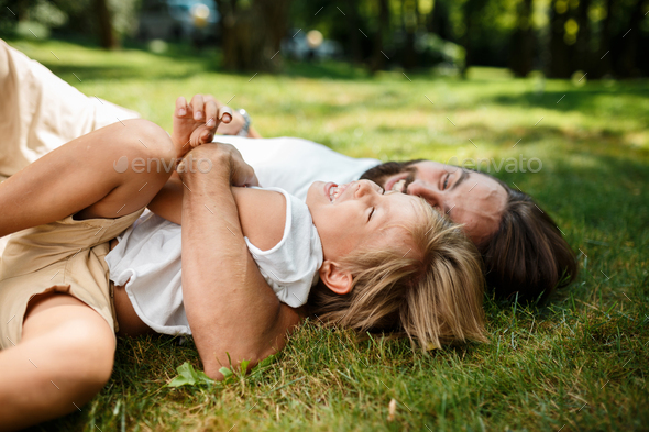 Dark haired man with a beard lies with little boy on a green lawn in the fresh air and laughing - Stock Photo - Images
