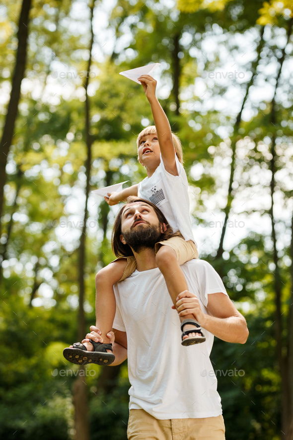 Walking in the forest. Blond boy dressed in a white t-shirt sitting on the shoulders of his bearded - Stock Photo - Images