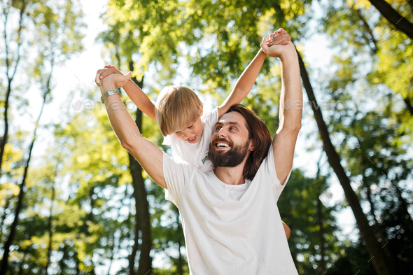 Father with his little son are dressed in the white t shirts. They are fooling around outdoor with - Stock Photo - Images