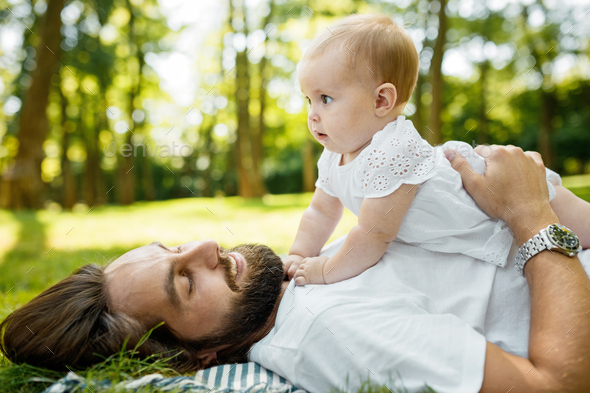 Little charming girl dressed in the white dress is lying on the father's chest outdoor on a warm - Stock Photo - Images