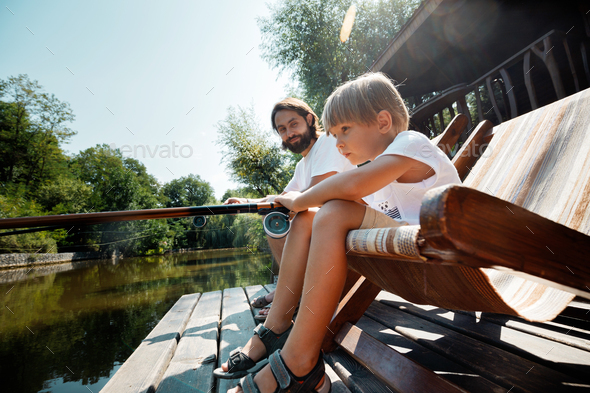 Little blond boy and his handsome father are sitting in recliners on the wooden pier and fishing - Stock Photo - Images