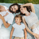 Mom dad and two children dressed in white casual clothes lie and smile on a striped plaid on a lawn - PhotoDune Item for Sale