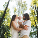 Happy family on the open air. Young dark-haired woman and her husband are kissing their charming - PhotoDune Item for Sale