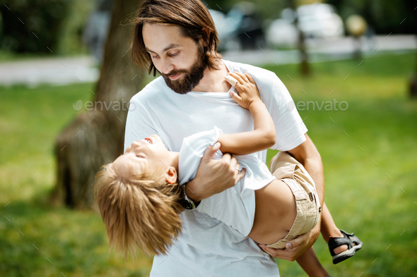 Handsome dark-haired father with beard dressed in the white t-shirt is holding in the arms his - Stock Photo - Images