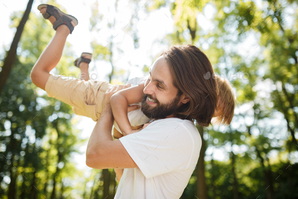 Dark-haired father with beard dressed in the white t-shirt is holding in the arms his blond son and - Stock Photo - Images