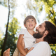 Handsome dark-haired father with beard dressed in the white t-shirt is holding in the arms his - PhotoDune Item for Sale