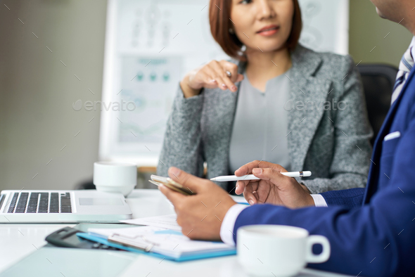 Business people using smartphone at meeting - Stock Photo - Images