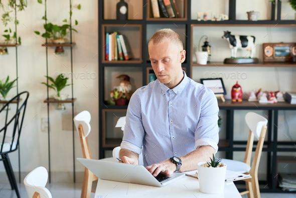 Coffee shop manager using laptop at table - Stock Photo - Images