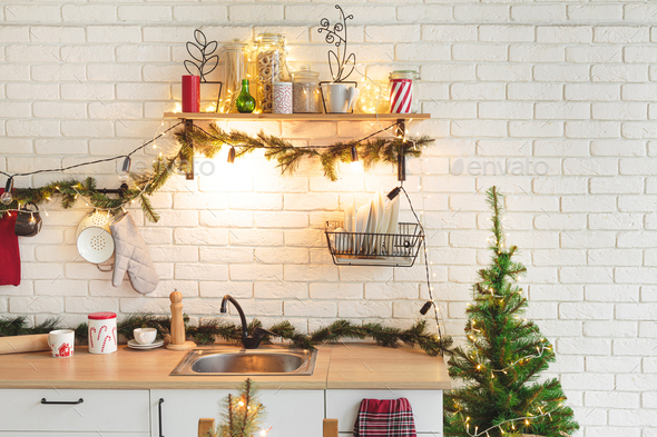 Interior white kitchen with lights and red christmas decorations - Stock Photo - Images
