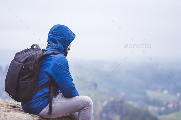 Lonely hiker wear outdoor clothing with backpack sitting on mountain edge, enjoying view of - Stock Photo - Images