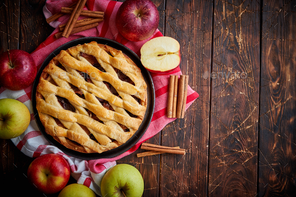 Homemade pastry apple pie with bakery products on dark wooden kitchen table - Stock Photo - Images