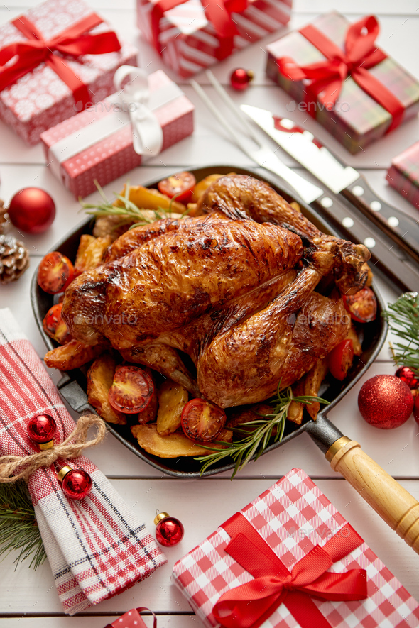 Roasted whole chicken or turkey served in iron pan with Christmas decoration - Stock Photo - Images