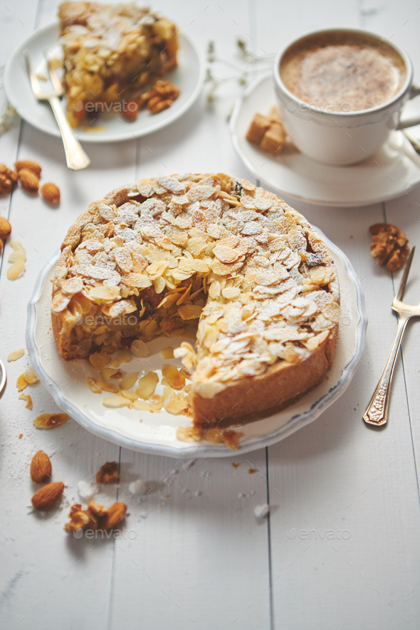 Whole delicious apple cake with almonds served on wooden table - Stock Photo - Images