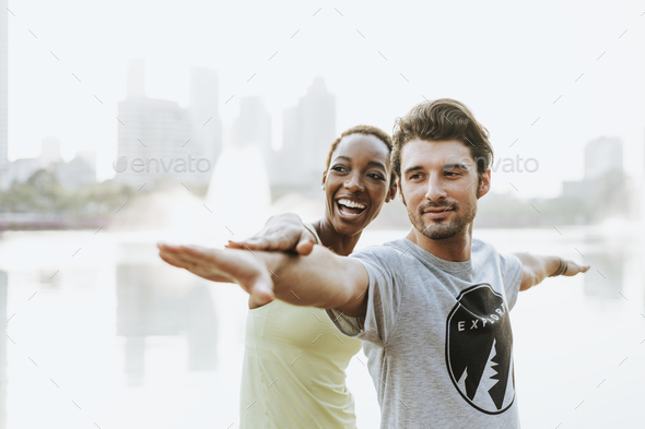 Couple doing a yoga in a park - Stock Photo - Images